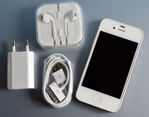 Image of an iphone with the headphones, usb cable and ac adapter