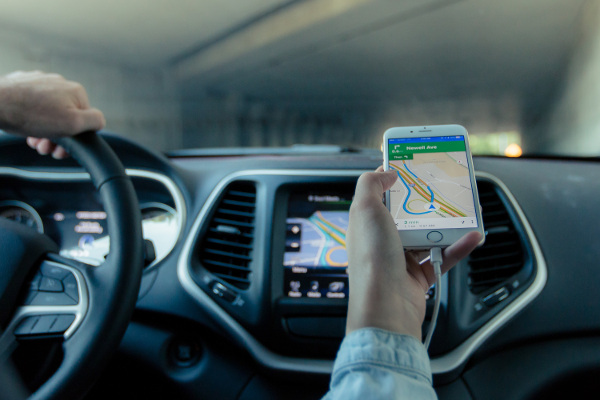 This is an image of a person holding a smartphone with their GPS navigation pulled up while driving in a car that also has GPS navigation