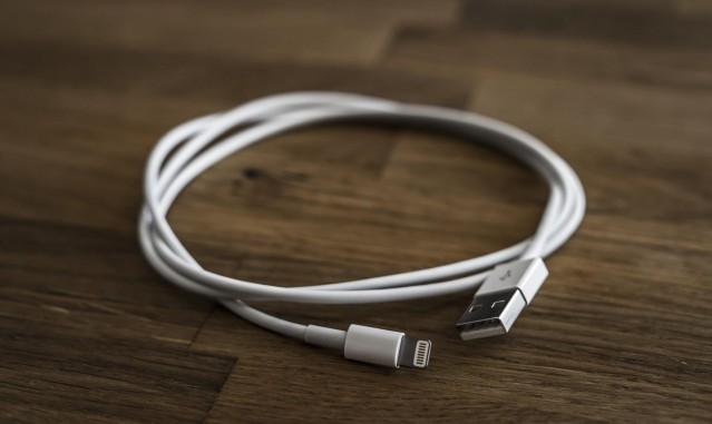 White USB cable laying on a wooden tagble